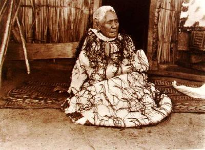 Elderly woman wrapped in korowai - moko - short white hair