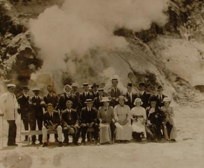 Tourist party with guide posed in front of an active geothermal formation, probably Waimangu, Rotorua