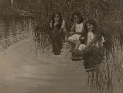 Three girls sitting in water