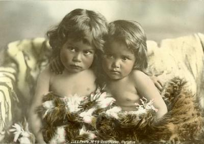 Two infants partly covered with feather cloak
