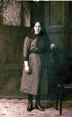 Postcard of studio portrait featuring young woman standing with left hand resting on chair