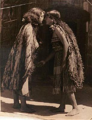 2 maori women in front of whare doing hongi, in cloaks and piupiu