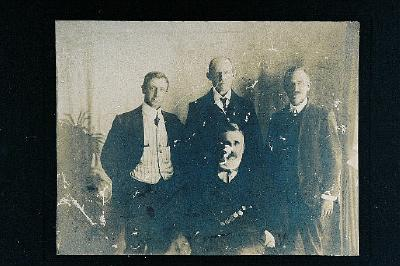 Unidentified man with bowling? medal's sitting, and three men standing behind him.