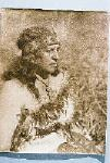 Maori woman sitting on the ground (facing right, almost profile view)